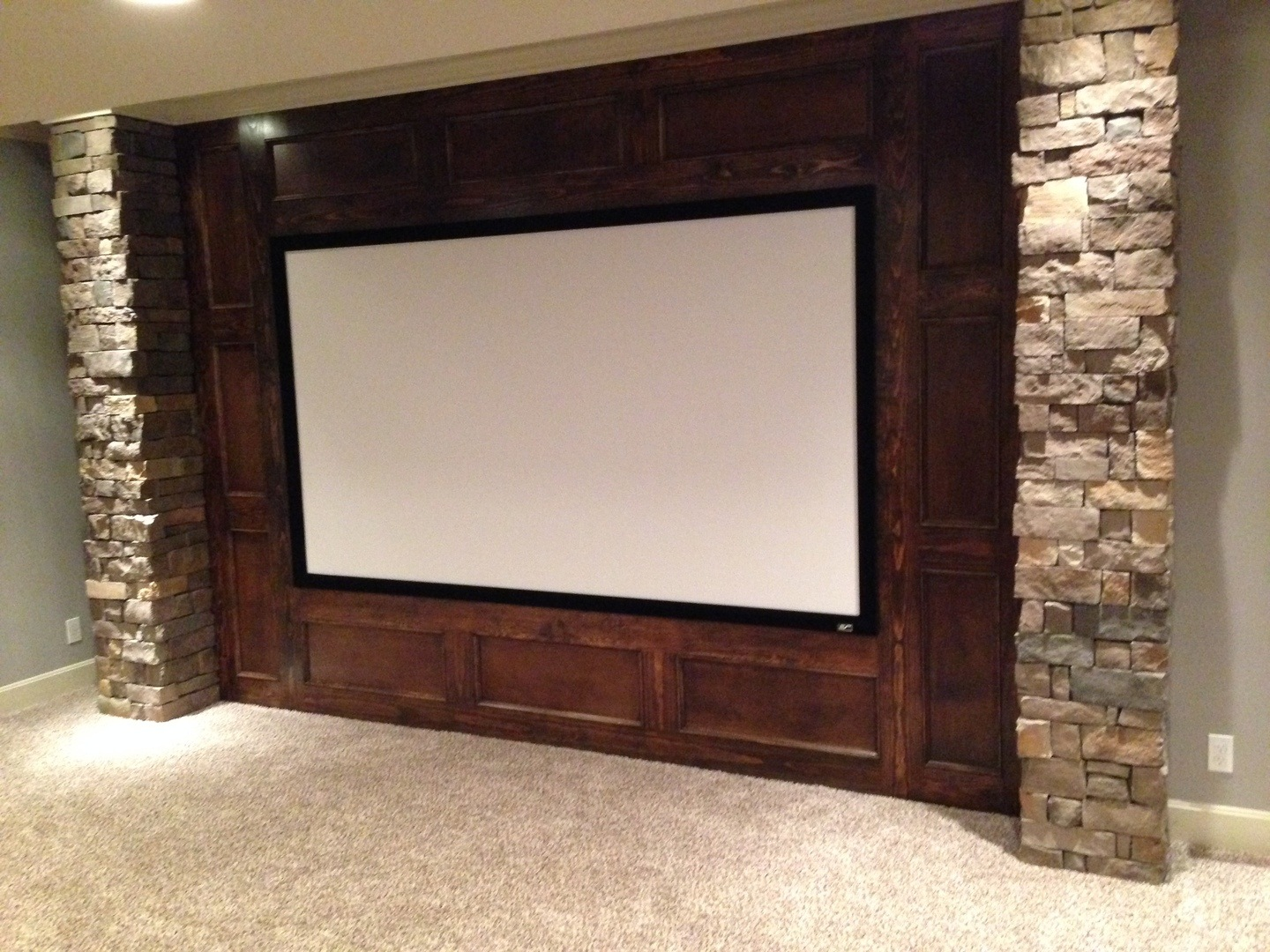 a giant flat screen is set in brick and stone to create the ultimate man cave
